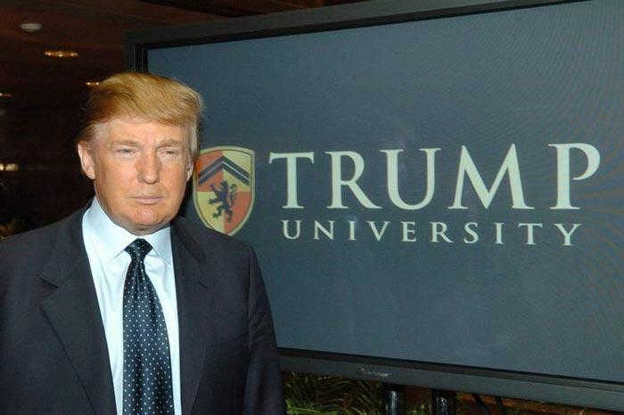 Donald Trump in front of Trump University logo